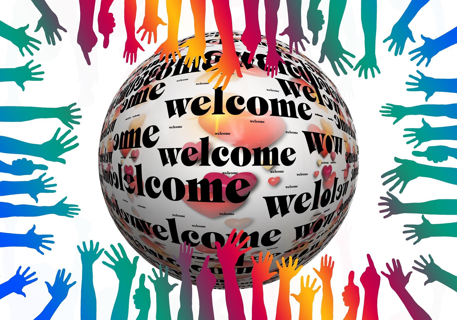Welcome-tekstillä maapallo, jota tavoittelee eriväriset ja -kokoiset kädet.